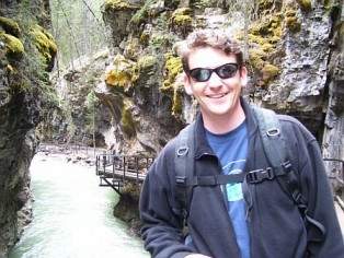 Image of Dr. Joe Casola smiling wile posing near a rushing river.